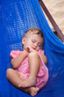 Little baby girl asleep outdoors on a hammock at the sea beach