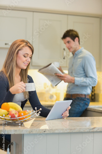 Woman with beverage and tablet computer and man with newspaper