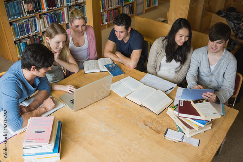 Students learning with laptop and tablet  in a library