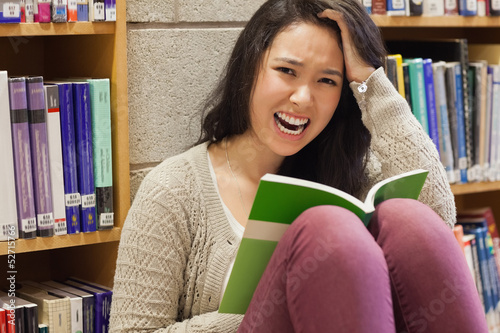 Stressed student reading in a library