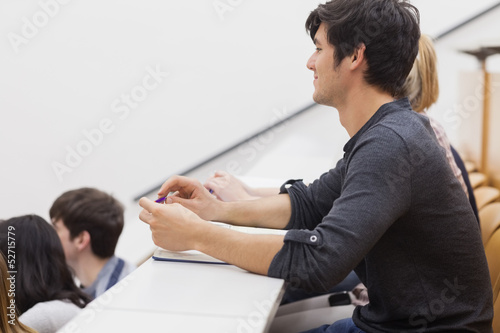 Student sitting in a lecture hall and listening the teacher