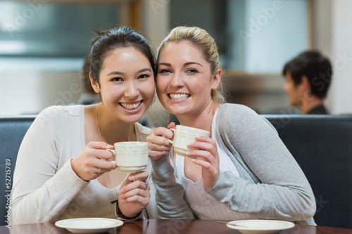 Two smiling students in college coffee shop