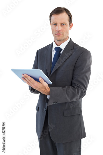 Serious charismatic businessman holding a tablet computer