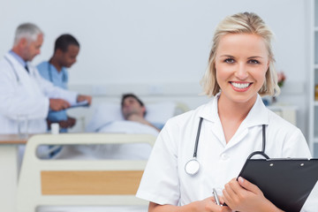 Nurse holding clipboard and looking at the camera