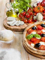 Italian pizza with tomato, mozzarella, basil and olives