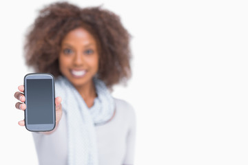 Woman with afro showing her smartphone