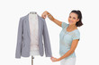 Fashion designer measuring blazer sleeve on mannequin and smilin