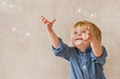 Very happy kid trying to catch soap bubbles
