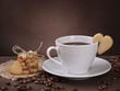Cup of coffee with cookie on brown background