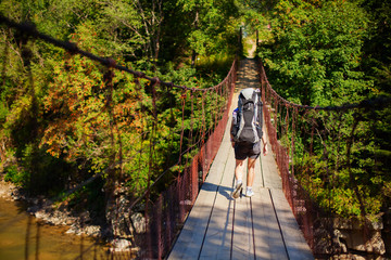 Woman hiker goes through suspension bridge