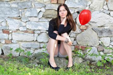 Frau sitzend mit Luftballon