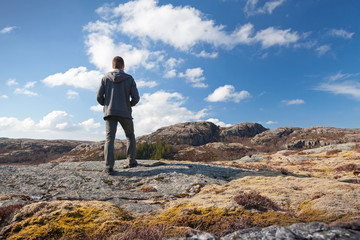 Young man stands on the rock and looks over horizon
