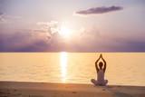 Fototapety Caucasian woman practicing yoga at seashore