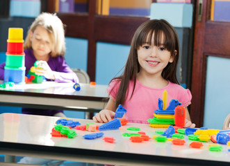 Girl With Construction Block While Friend Playing In Background