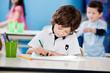 Boy Drawing With Sketch Pen At Desk In Kindergarten