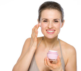 Beauty portrait of young woman applying creme