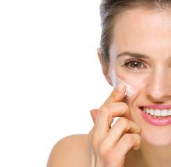 Closeup on happy young woman applying creme on cheek