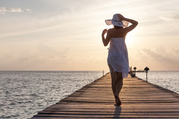 Caucasian woman takes rest at wooden pier to Indian ocean