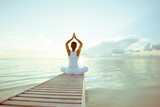 Caucasian woman practicing yoga at seashore - Fine Art prints