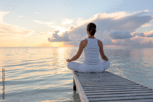 Caucasian woman practicing yoga at seashore - 52723757
