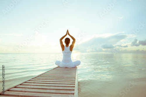 Caucasian woman practicing yoga at seashore - 52723787