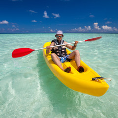 Young caucasian man kayaking in sea at Maldives