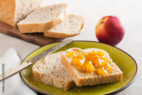 Spelt bread slices on a dish with peach marmalade