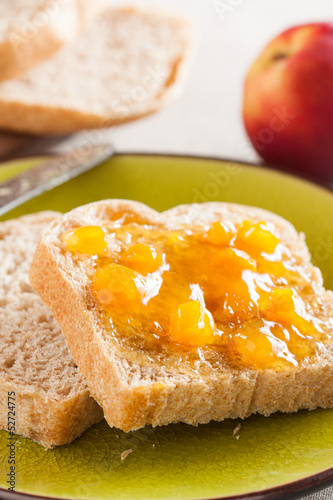 Spelt bread slices on a dish with peach marmalade close-up