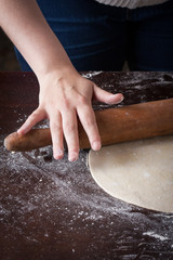 Hand on a rolling pin preparing pizza dough