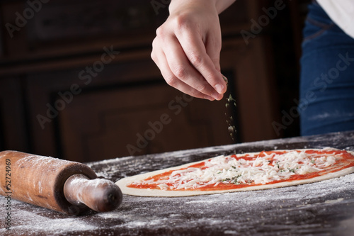 Cook putting oregano on raw pizza
