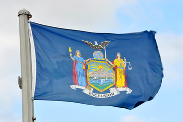 Flag of New York State in blue sky background