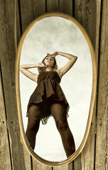 thoughtful woman with her reflection in mirror