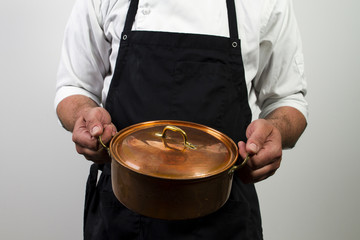chef holding copper pan