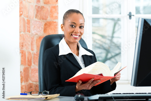 Lawyer in her office with law book on computer