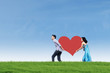 Couple bring heart card on green field
