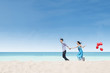 Running couple at beach wih balloons