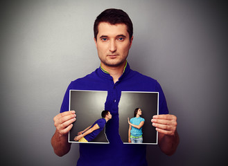 man holding the lacerated photo of young couple