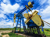 Oil and gas well detail profiled on blue sky with clouds