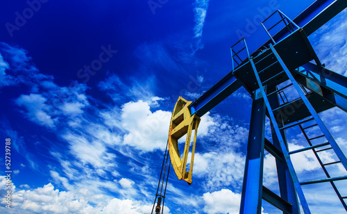 Oil and gas well detail profiled on blue sky with clouds - 52739788