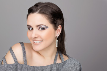 Elegant young woman wearing sparkling dress and makeup