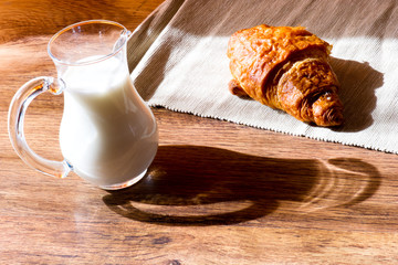 glass jug of milk with  croissant  on wooden table