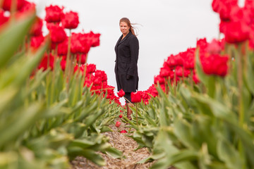 Woman standing in a field of tulips
