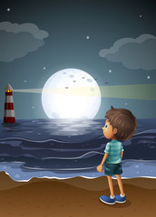 A young boy watching a fullmoon at the beach