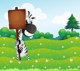 A zebra holding an empty wooden board