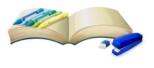 An empty book with crayons, a stapler and an eraser