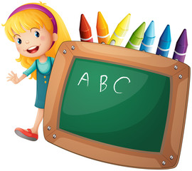 A young girl beside a blackboard and crayons