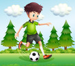 A boy kicking the ball near the pine trees