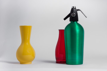Still life of red bottle yellow vase and green seltzer siphon