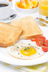 Fried eggs, fresh tomatoes and crunchy toast for breakfast