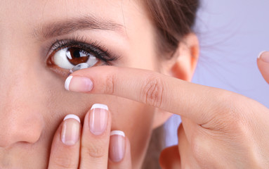 Young woman putting contact lens in her eye close up
